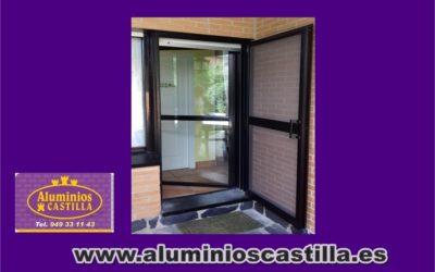 Puerta Abatible de aluminio de una hoja en lacado negro fabricada a medida por Aluminios Castilla, máxima calidad para su vivienda.