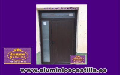 Puerta de aluminio lacado oxido con panel , vidrio y cerradura de seguridad .